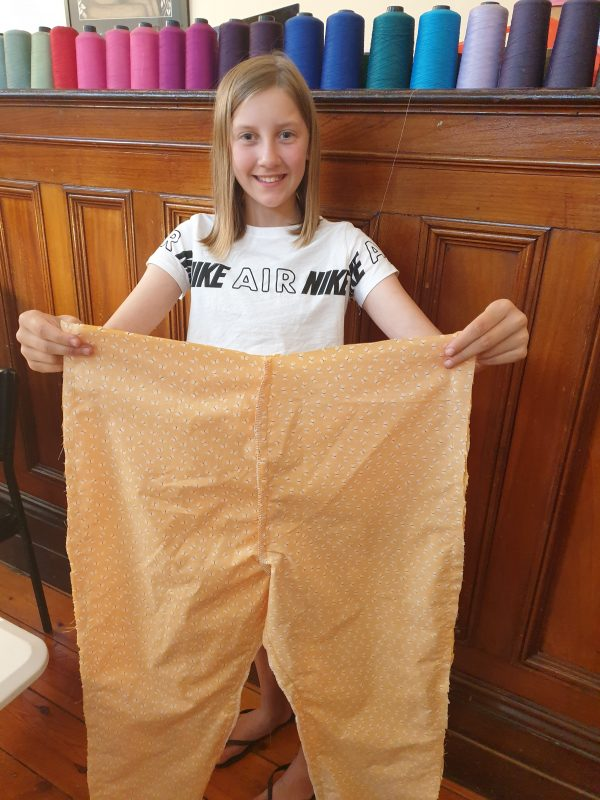 kid holding up pair of pants with big smile on their face