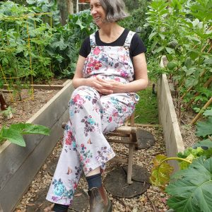 woman wearing floral overalls seated in a garden looking happy