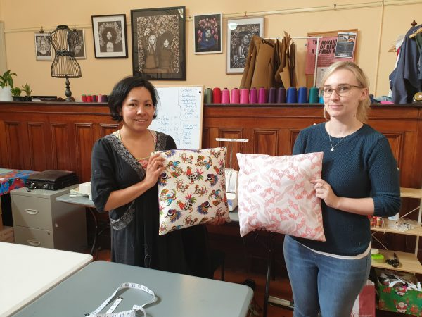 Two women proudly showing their handmade cushions