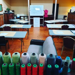 sewing studio with desks ready for class, row of coloured cotton in the foreground